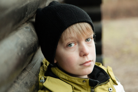 log cabin winter: Close up of sad young boy in hat and yellow winter coat sitting against log cabin wall outdoors Stock Photo
