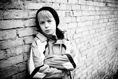 expression facial: Single boy in winter coat and black hat with folded arms and sad facial expression next to old brick wall outdoors Stock Photo