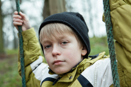 swing set: Close up view on solemn blond male child in yellow coat and black knitted hat holding on to ropes for swing set in park outdoors Stock Photo