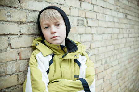 sickly: Single male child in winter coat and black hat with folded arms and dejected or sickly expression while leaning against brick wall with copy space Stock Photo
