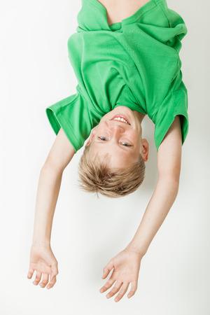 cabeza abajo: Un solo ni�o rubio al rev�s en la camisa verde con los brazos extendidos mientras que cuelga sobre el fondo blanco Foto de archivo