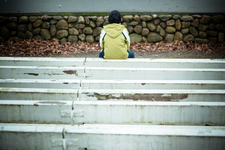 friendless: Back of single lonely child in coat and hat sitting on painted white bench near wall of stones with copy space