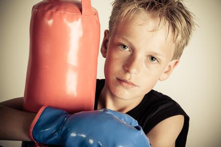 dimly: Serious blond boy wearing black shirt and blue boxing gloves hugs punching bag in dimly lit room