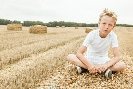 Boy wearing white shirt and shorts sits cross legged and alone in harvested wheat field with bales of hay in the distance behind him