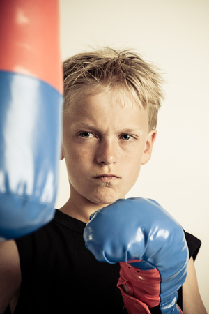 pugilist: Frowning blond boy with spiky hair wearing black sleeveless shirt and blue boxing gloves against a light brown background Stock Photo