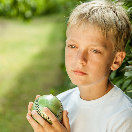 lost in thought: Boy with far off look and wearing white shirt stands alone in yard holding green baseball while lost in thought