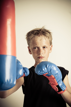 spiky hair: Solitary serious blond boy with spiky hair wearing black sleeveless shirt strikes red and blue punching bag with boxing gloves
