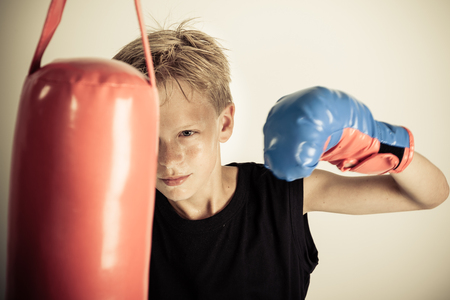 pugilist: Blond boy with spiky hair wearing black sleeveless shirt swings single gloved hand at red punching bag