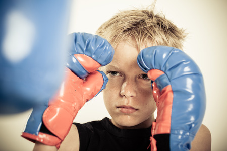 Single serious blond sweating child with blue and red boxing gloves focusing on punching pad during practice Stock Photo