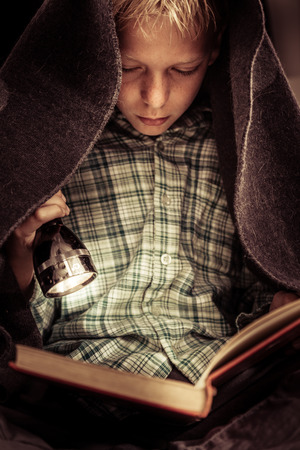 hard cover: Cute serious child in green flannel shirt reading hard cover book under blanket covers with flashlight Stock Photo
