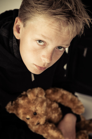 Single sad little boy holding cute brown plush bear toy in his arms while leaning over and looking upwards