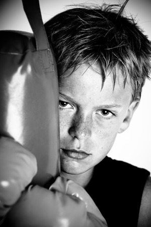 pugilist: Sweating child wearing boxing gloves and dark sleeveless shirt leaning against punching pad in black and white Stock Photo