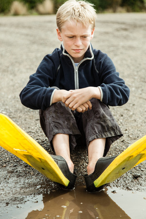 single child: Single child daydreaming while sitting on ground next to muddy puddle in gravel while wearing yellow and black diving flippers