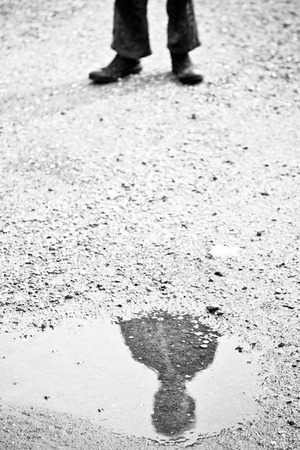 obscured face: Black and white reflection of obscured child face in puddle surrounded by gravel outdoors with copy space Stock Photo