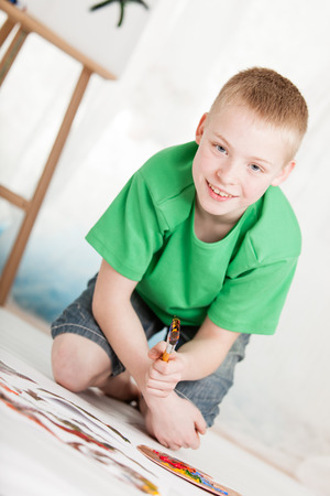 slanted: Slanted view of boy in green shirt and blue jean shorts kneeling on painting near easel on light background
