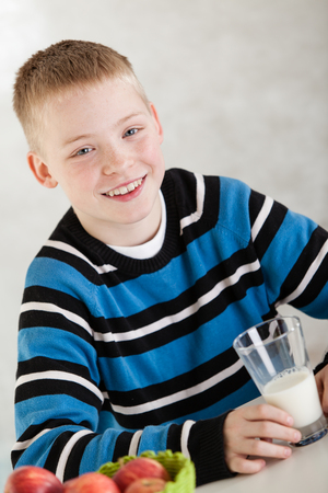 milk mustache: Handsome single blond boy wearing milk mustache over lip while holding half empty glass at table indoors