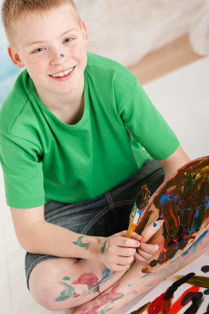daubed: Slanted view of boy wearing shorts and green shirt with paint on legs and hands and holding brush and color pallet