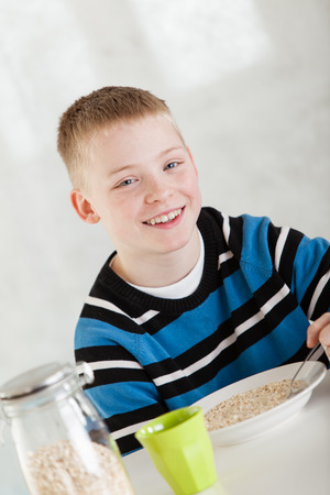 giggling: Single giggling blond child in blue and white shirt with happy expression next to sealed glass jar and cup while eating from bowl of oatmeal at table