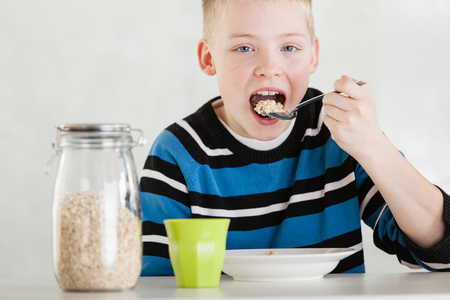 Single hungry blond child in blue and white shirt next to sealed glass jar of cereal and cup while putting oatmeal in his mouth at table