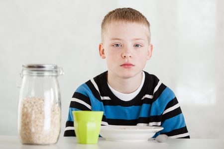 deadpan: Serious blond child in blue and white shirt with bored expression next to sealed glass jar of oats and bowl on table Stock Photo
