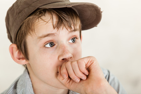 wide eyed: Close up on wide eyed poor child wearing worn out brown hat with anxious expression and closed hand near mouth