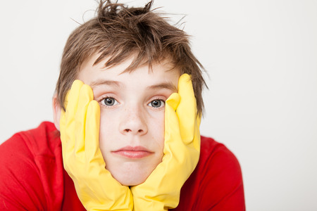 Bored single child in red shirt and messy hair wearing yellow rubber gloves with hands on face next to copy space