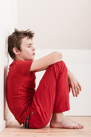 sit: Side profile view on single withdrawn and tired boy in red pants and shirt sitting on floor against wall with copy space
