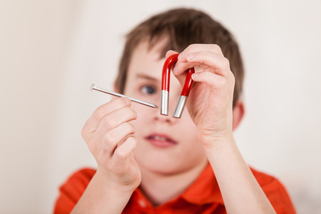 Selective focus close up on hands of boy moving large iron nail next to red and white magnet with curious face in background
