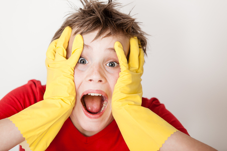 messy hair: Single screaming child in red shirt and messy hair wearing yellow rubber gloves with hands on face next to copy space