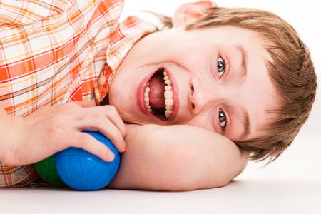 Schließen Sie oben auf einzelne schreien männliches Kind mit überschwänglichen Ausdruck Kind Verlegung seitlich auf den Arm mit zwei Plastikkugeln in der Hand