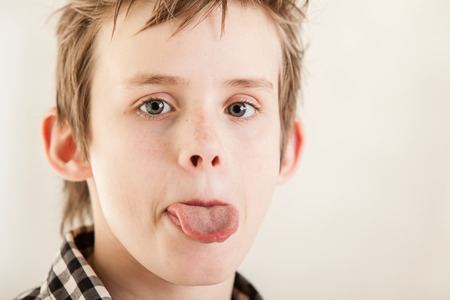children face: Close up with copy space on rude male child in plaid shirt and messy hair with tongue sticking out Stock Photo