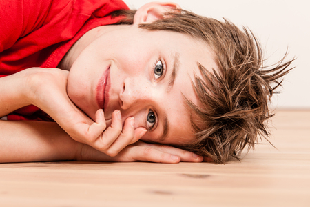 pert: Sideways close up on head of happy boy in red shirt lying on hardwood floor with hands near face