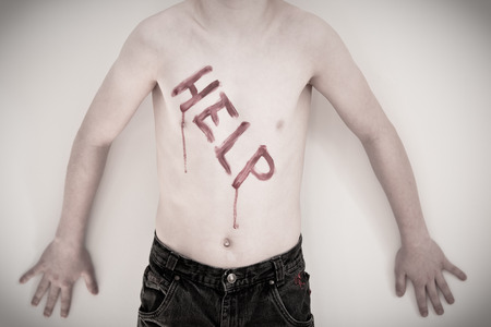 splayed: Single unidentifiable shirtless boy with bloody letters spelling help written on chest for abuse or neglect concept Stock Photo