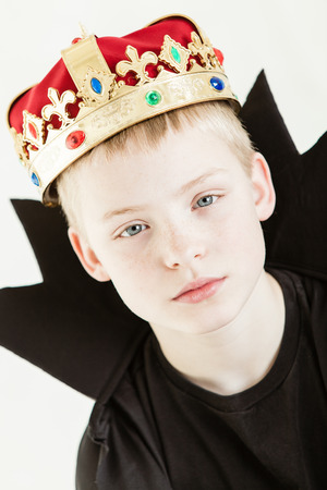 pointy: Serious blond boy dressed in black gown with long pointy collar and gold and red velvet crown studded with colorful jewels