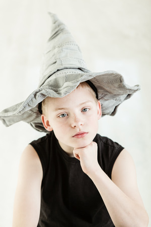closed fist: Serious blond boy dressed in gray pointed hat and black sleeveless shirt while resting chin on closed fist Stock Photo