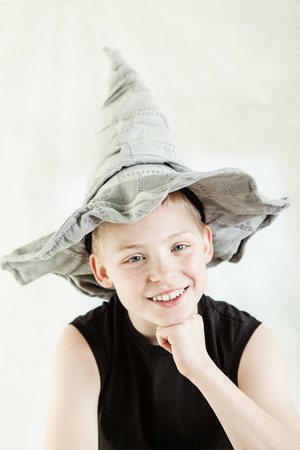 dunce cap: Happy blond boy dressed in gray pointed hat and black sleeveless shirt while smiling and resting chin on closed fist