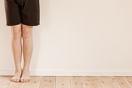 bare feet boys: Pair of bare feet and legs of child wearing black shorts over hardwood flooring with copy space on white wall