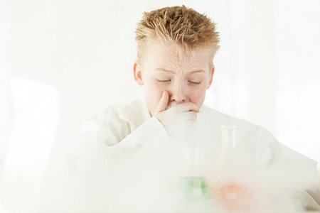 Coughing young boy wearing white lab coat and spiky blond hair surrounded by dangerous chemicals reacting and smoking in glass beakers Stock Photo