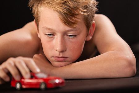 niño sin camisa: Joven adolescente acostado boca abajo jugando con un modelo brillante coche rojo colorido mirarlo con una expresión pensativa mientras empuja con la mano Foto de archivo