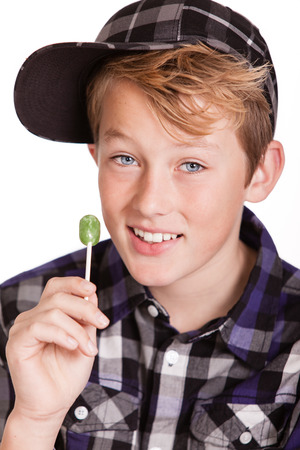 skewed: Happy trendy young boy wearing a skewed baseball cap holding a green lollipop in his hand as he smiles at the camera