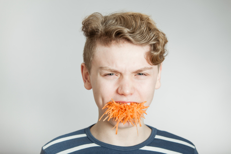 mouthful: Handsome young boy with a mouthful of grated fresh raw carrot frowning in repulsion to show his distaste ad it overflows from his mouth Stock Photo