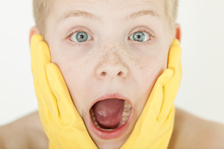 agape: Shocked boy with bright green eyes and mouth agape holds yellow rubber gloves against his face on a light background