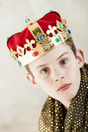 make believe: Tilt angle view on single serious young boy in large sparkling gold robe and wide brim and red velvet jeweled crown