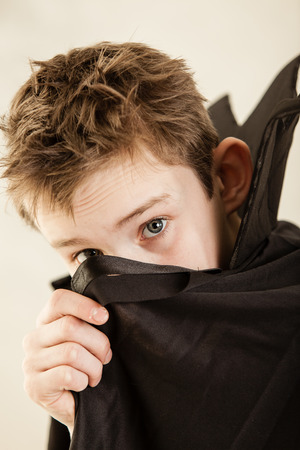 malevolent: Single cute little boy dressed in black vampire cloak using hand to cover part of his face over white background