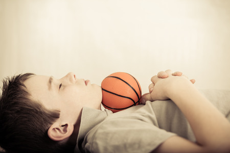 near side: Side profile view on single cute child asleep with little basketball under chin and folded hands on chest
