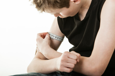 flexed: Close up of male youth holding tape measure around flexed bicep muscle on arm over white background