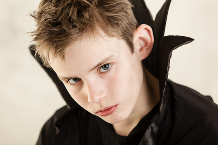 glowering: Single cute little boy with serious expression dressed in black vampire cloak over white background