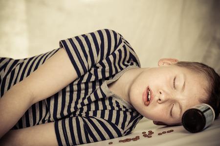 薬瓶と彼のそばに錠が付いている床に横たわる意識不明の男性子供の地面レベルのビューを閉じる角度