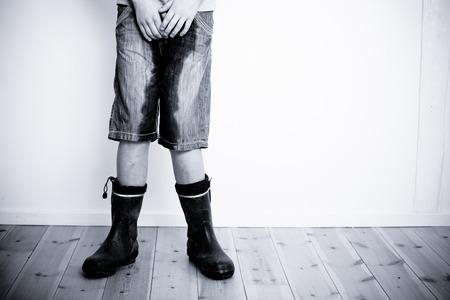 Las piernas de adolescente en pantalones vaqueros cortos pantalones mojados con agua u orina de pie en el piso de madera con copia espacio en la pared