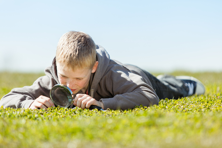 Ground level view on cute blond boy in gray sweater with curious expression using magnifying glass over field of grass